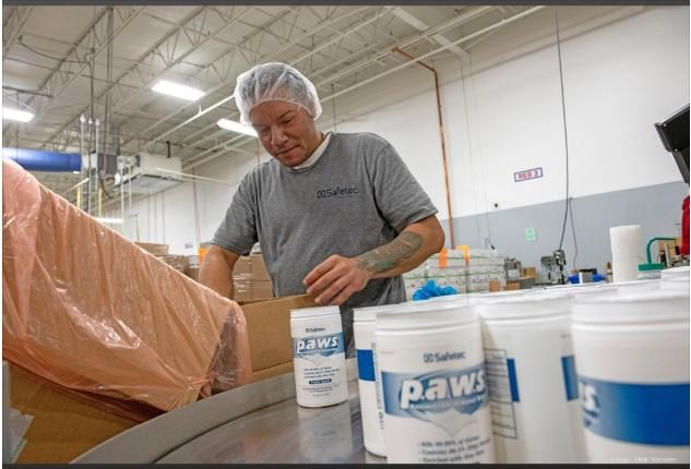 Juan Rivera, an employee at Safetec of America in Buffalo, works near the company's p.a.w.s. Antimicrobial Hand Wipes products, which are formulated with 66.5% ethyl alcohol to kill 99.99% of germs, according to Safetec literature. (file photo) MARK WEBSTER